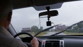 El hombre está conduciendo a lo largo del camino en coche almacen de video