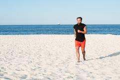 El hombre está corriendo en la playa Hombre que hace ejercicio en la costa Imagen de archivo