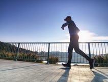 El hombre está corriendo rápidamente en el puente de la orilla Silueta del hombre activo imagenes de archivo