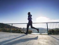 El hombre está corriendo rápidamente en el puente de la orilla Silueta del hombre activo fotos de archivo libres de regalías