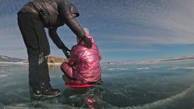 El hombre está dando vuelta a la mujer en el hielo El padre da vuelta a su hija y a su madre en un hielo La familia tiene la dive almacen de metraje de vídeo