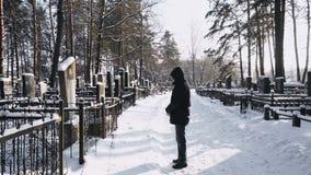 El hombre está de luto o se aflige para el hombre muerto en cementerio o cementerio en invierno en bosque metrajes