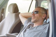 El hombre está descansando en el coche Fotos de archivo