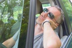 El hombre está descansando en el coche Imágenes de archivo libres de regalías