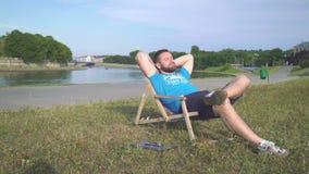 El hombre está descansando sobre sunbad al lado del río metrajes