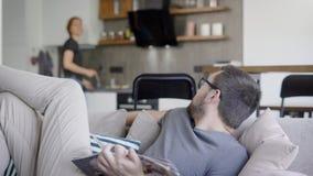 El hombre está descansando sobre un sofá con la revista adentro el domingo por la mañana, su esposa joven está cocinando con la e metrajes