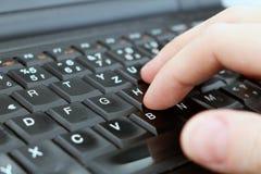 El hombre está escribiendo con el teclado del ordenador portátil Imagen de archivo libre de regalías