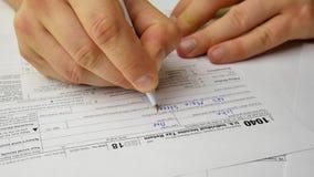 El hombre está escribiendo contribuye la información en la forma individual 1040 de la declaración sobre la renta de los E.E.U.U. almacen de video