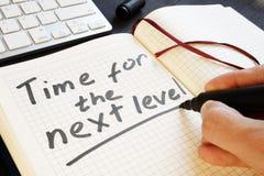 El hombre está escribiendo la hora para el nivel siguiente Motivación fotos de archivo libres de regalías