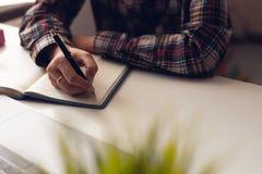 El hombre está escribiendo un mensaje en el libro en la tabla Él ahora está sentando el plan empresarial imagen de archivo