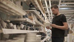 El hombre está examinando las placas de cerámica en tienda de la loza, está retirando y está poniendo almacen de video