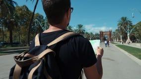 El hombre está examinando el mapa del transporte de la ciudad, mirando alrededor en la calle metrajes