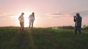 El hombre está fotografiando a dos mujeres embarazadas contra la perspectiva de una puesta del sol rosada metrajes