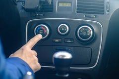 El hombre está girando el sistema de aire acondicionado del coche Imágenes de archivo libres de regalías