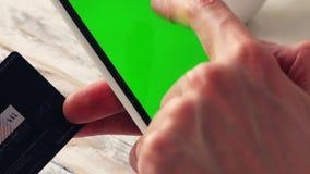 El hombre está haciendo compras en línea con el teléfono móvil, pantalla verde vacía Cierre para arriba almacen de video