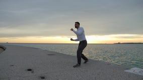 El hombre está haciendo ejercicios del boxeo en el ebankment Atleta que entrena al aire libre Salida del sol almacen de video