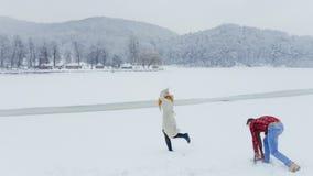 El hombre está haciendo una bola de nieve mientras que su amante principal rojo está corriendo lejos a lo largo del prado nevoso fotos de archivo