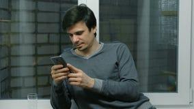 El hombre está hojeando las páginas de Internet en el teléfono móvil que se coloca cerca de la ventana en el balcón almacen de video