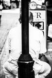 El hombre está inclinando el suyo de nuevo a la lámpara de calle Imagen de archivo libre de regalías
