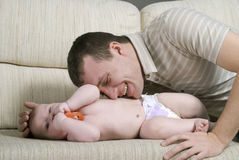 El hombre está jugando con el bebé Fotos de archivo
