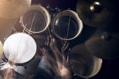 El hombre está jugando el tambor fijado en fondo de la luz corta fotos de archivo libres de regalías