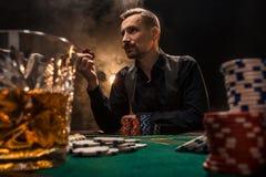 El hombre está jugando el póker con un cigarro y un whisky Un hombre que gana todos los microprocesadores en la tabla con el ciga Fotos de archivo