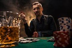 El hombre está jugando el póker con un cigarro y un whisky Un hombre que gana todos los microprocesadores en la tabla con el ciga Fotografía de archivo