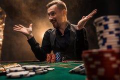 El hombre está jugando el póker Un hombre que gana todos los microprocesadores en la tabla con el cigarrillo grueso fuma El conce Imagen de archivo