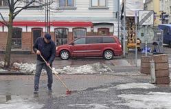 El hombre está limpiando la plaza del mercado en Oulu, Finlandia fotografía de archivo