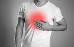 El hombre está llevando a cabo su dolor de pecho del pecho heartburn El hogar fotos de archivo