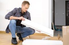 El hombre está llevando a cabo un tablero de los muebles fotos de archivo libres de regalías