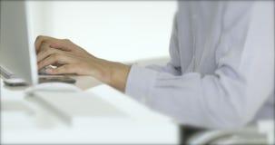 El hombre está mecanografiando el documento por el ordenador en oficina almacen de video