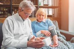 El hombre está midiendo la presión arterial de su esposa Él cuida sobre ella imagen de archivo