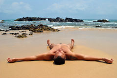 El hombre está mintiendo en la arena por el océano fotografía de archivo