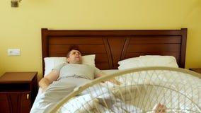 El hombre está mintiendo en la cama Calor del verano La fan está trabajando almacen de metraje de vídeo