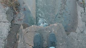 El hombre está mirando en descarga de la contaminación de agua del dren Piernas del ` s del hombre del primer metrajes
