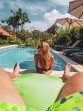 El hombre está mirando a la muchacha en la piscina Fotos de archivo libres de regalías