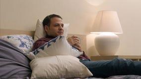 El hombre está mirando la TV y el té de consumición en la noche imagenes de archivo