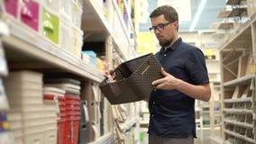 El hombre está mirando una cesta plástica en un supermercado, girándola a disposición almacen de metraje de vídeo