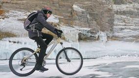 El hombre está montando la bicicleta cerca de la gruta del hielo La roca con las cuevas de hielo y los carámbanos es muy hermosa  Foto de archivo