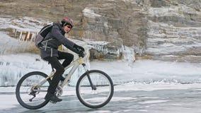 El hombre está montando la bicicleta cerca de la gruta del hielo La roca con las cuevas de hielo y los carámbanos es muy hermosa  Fotografía de archivo