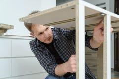 El hombre está montando los muebles en casa fotos de archivo libres de regalías