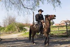 El hombre está montando un caballo foto de archivo