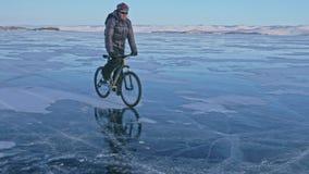 El hombre está montando una bicicleta en el hielo Visten al ciclista en una chaqueta, una mochila y un casco del gris abajo Hielo Imágenes de archivo libres de regalías