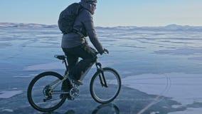 El hombre está montando una bicicleta en el hielo Visten al ciclista en una chaqueta, una mochila y un casco del gris abajo Hielo Foto de archivo