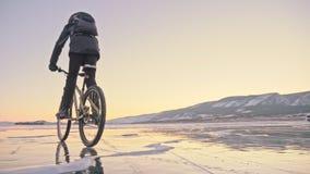 El hombre está montando una bicicleta en el hielo Visten al ciclista en una chaqueta, una mochila y un casco del gris abajo Hielo Fotos de archivo libres de regalías