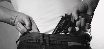 El hombre está ocultando un arma en el suyo detrás Foto de archivo libre de regalías