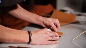 El hombre está pegando dos detalles de producto de cuero, poniendo uno sobre otro, primer almacen de video