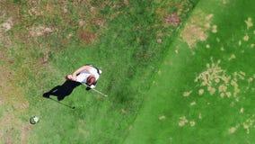 El hombre está pegando fuertemente una pelota de golf en una visión superior metrajes