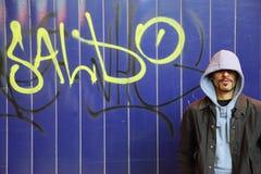 El hombre está permaneciendo la pared cercana con la pintada en una calle Imagenes de archivo